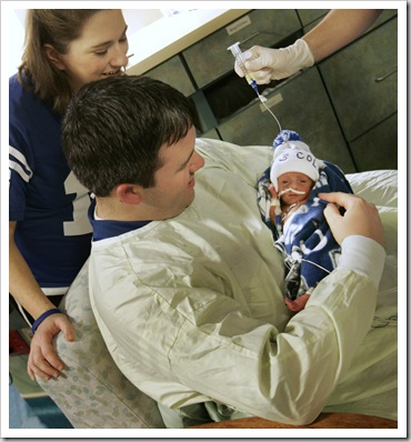 Jen and Brad Murray (cq) hold their son Brooks Layton Murray (cq) while he is being fed by Jenny Heminger, RN (cq, hand), at the St. Vincent Women's Hospital NICU, Friday, February 9, 2007.  Brooks was the second in a set of quadruplets born to Jen and Brad Murray last Friday, February 2, 2007.  He was three lbs at birth.  All four of the babies are in the NICU.  (Kelly Wilkinson / The Indianapolis Star)