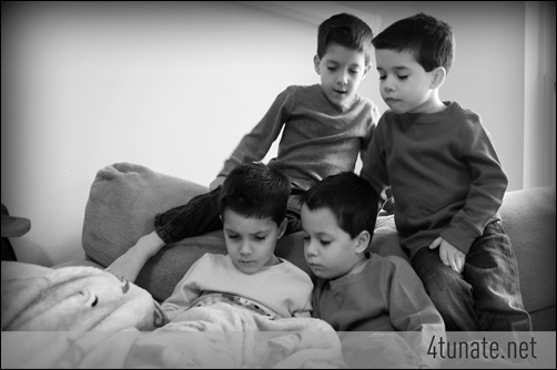 four brothers reading together on the couch