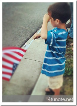 little boy salutes fallen solider and waves flag