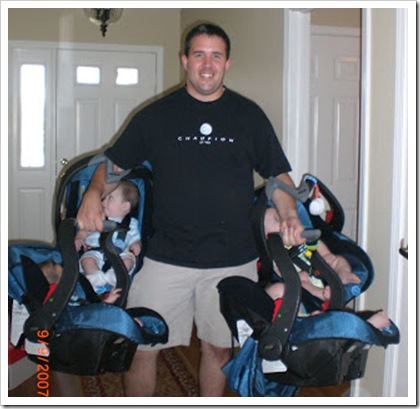 dad carrying all four carseats with quadruplets